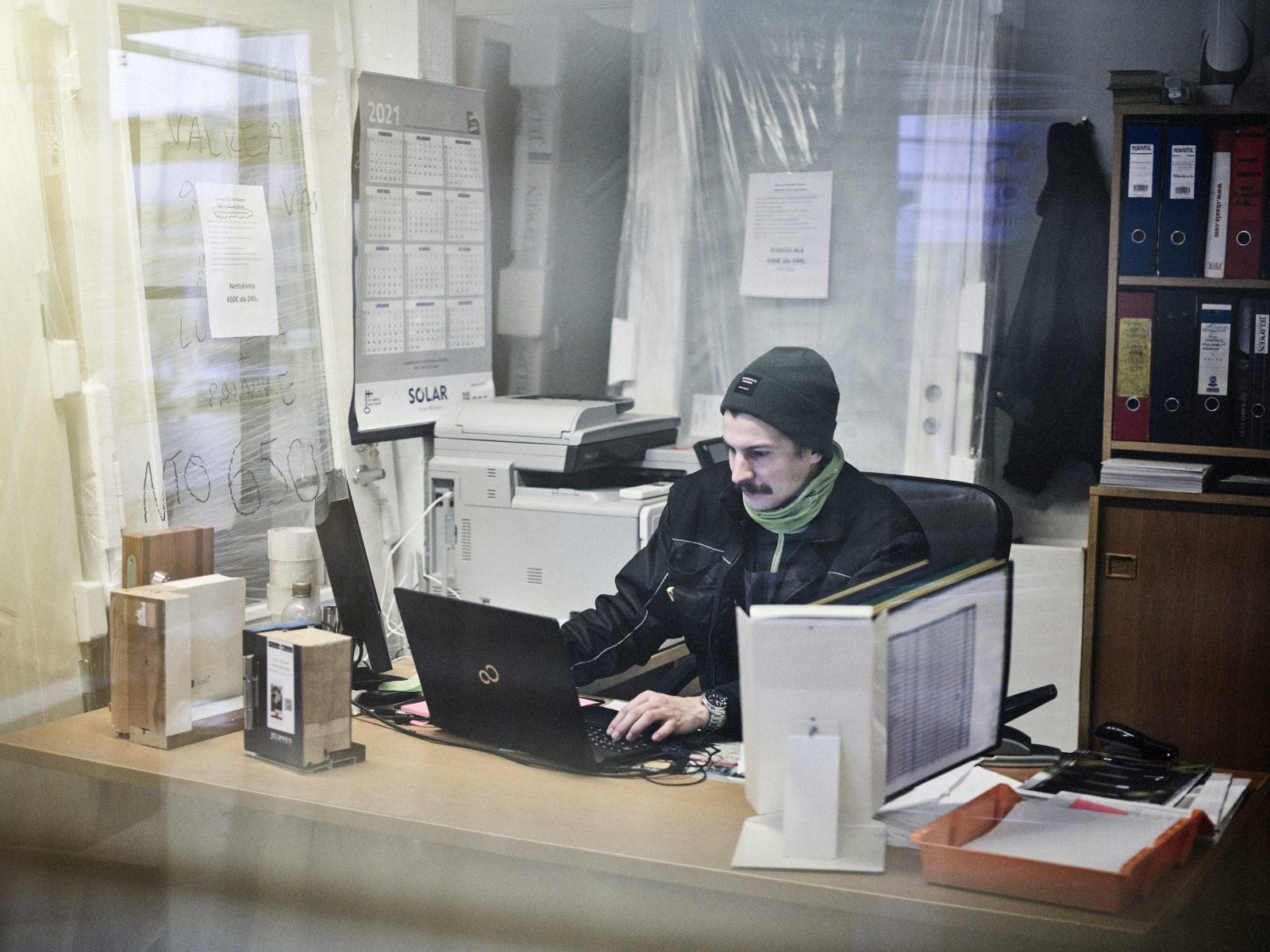 Myyjä vastaa sähköposti viesteihin työpisteellään.