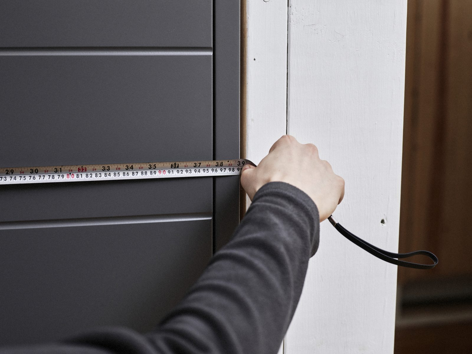 Mies mittaa mittanauhalla oven leveyttä.