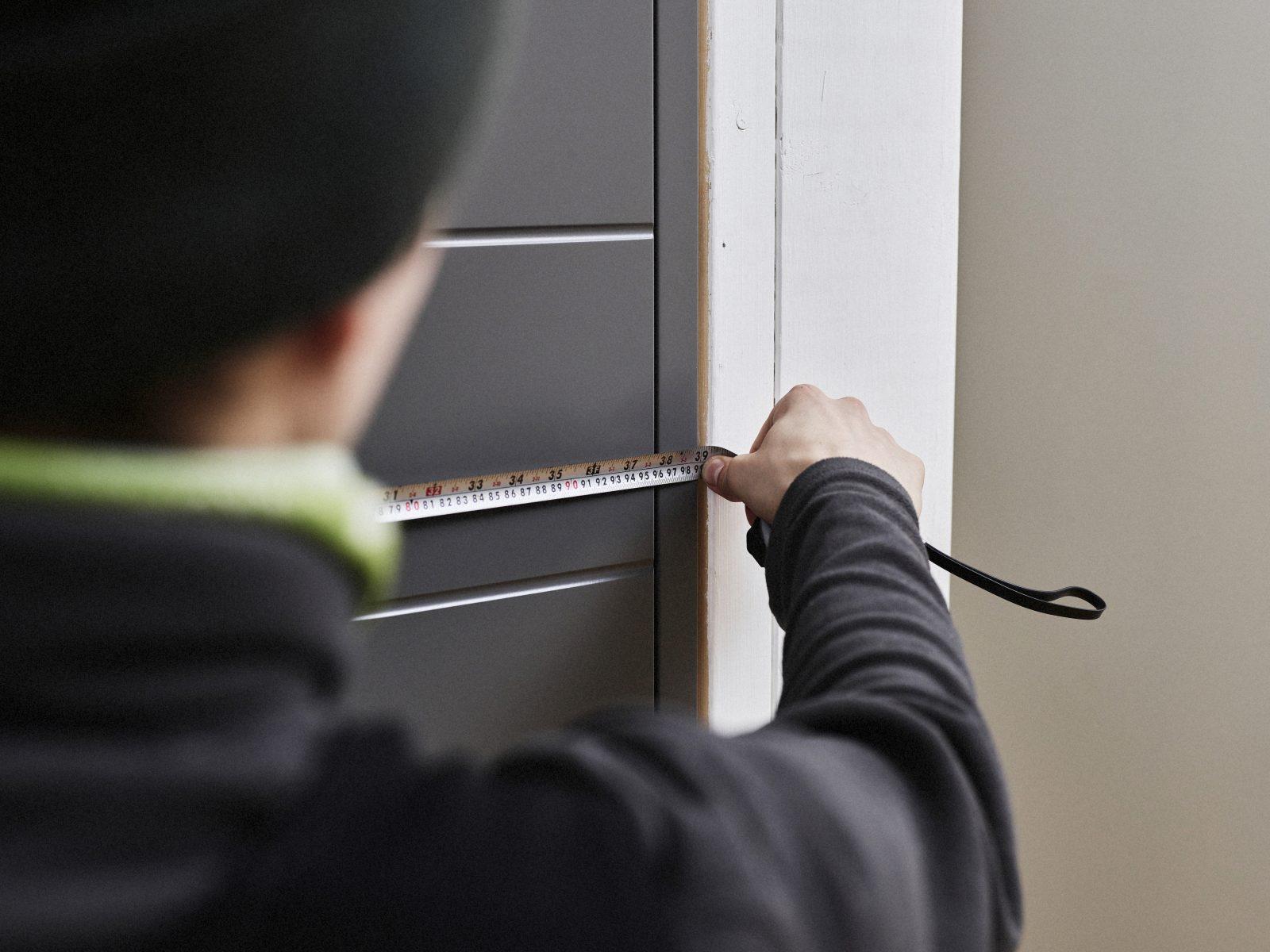 Mies mittaa oven leveyttä.