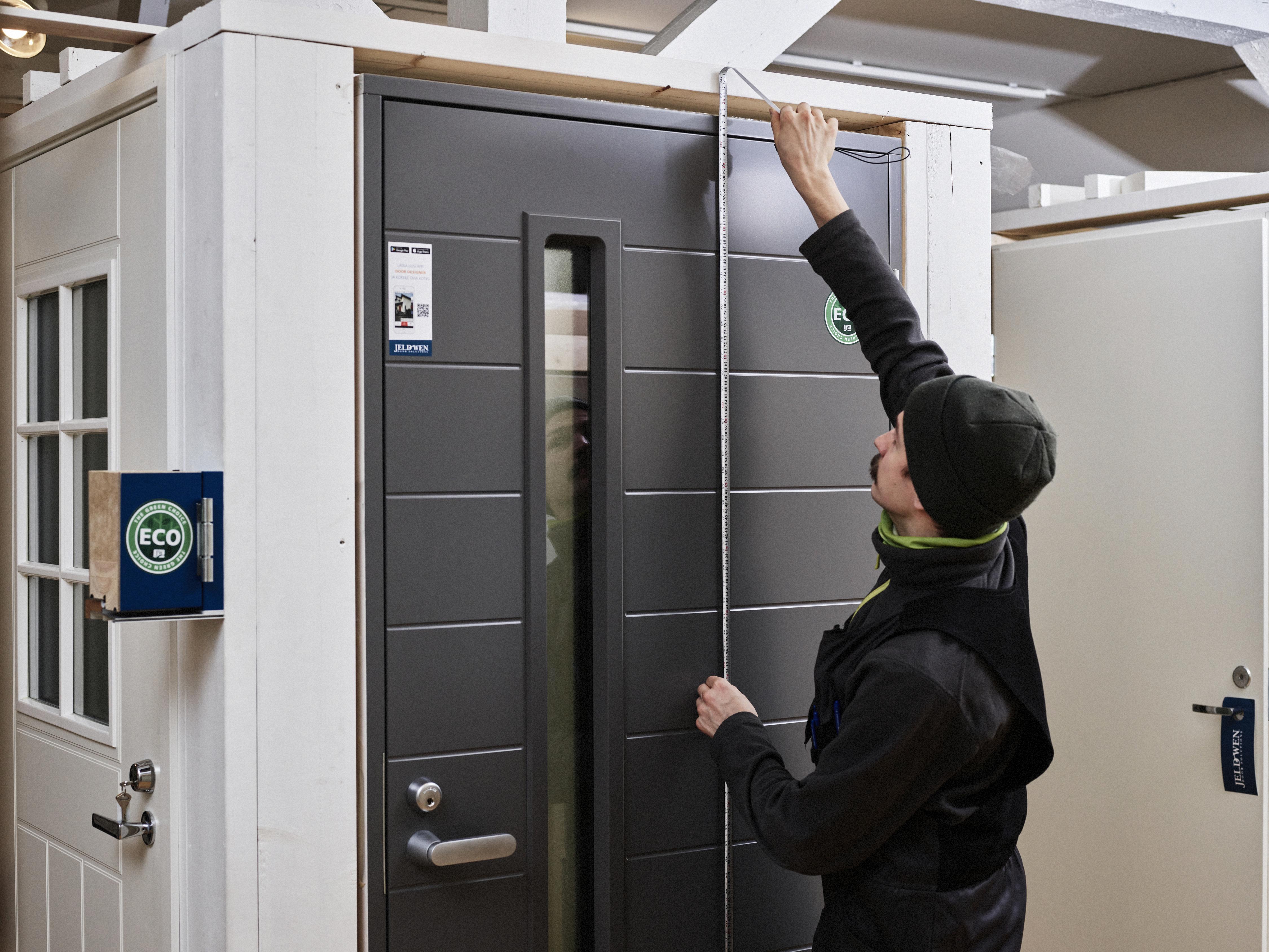 Mies mittaa oven korkeutta.