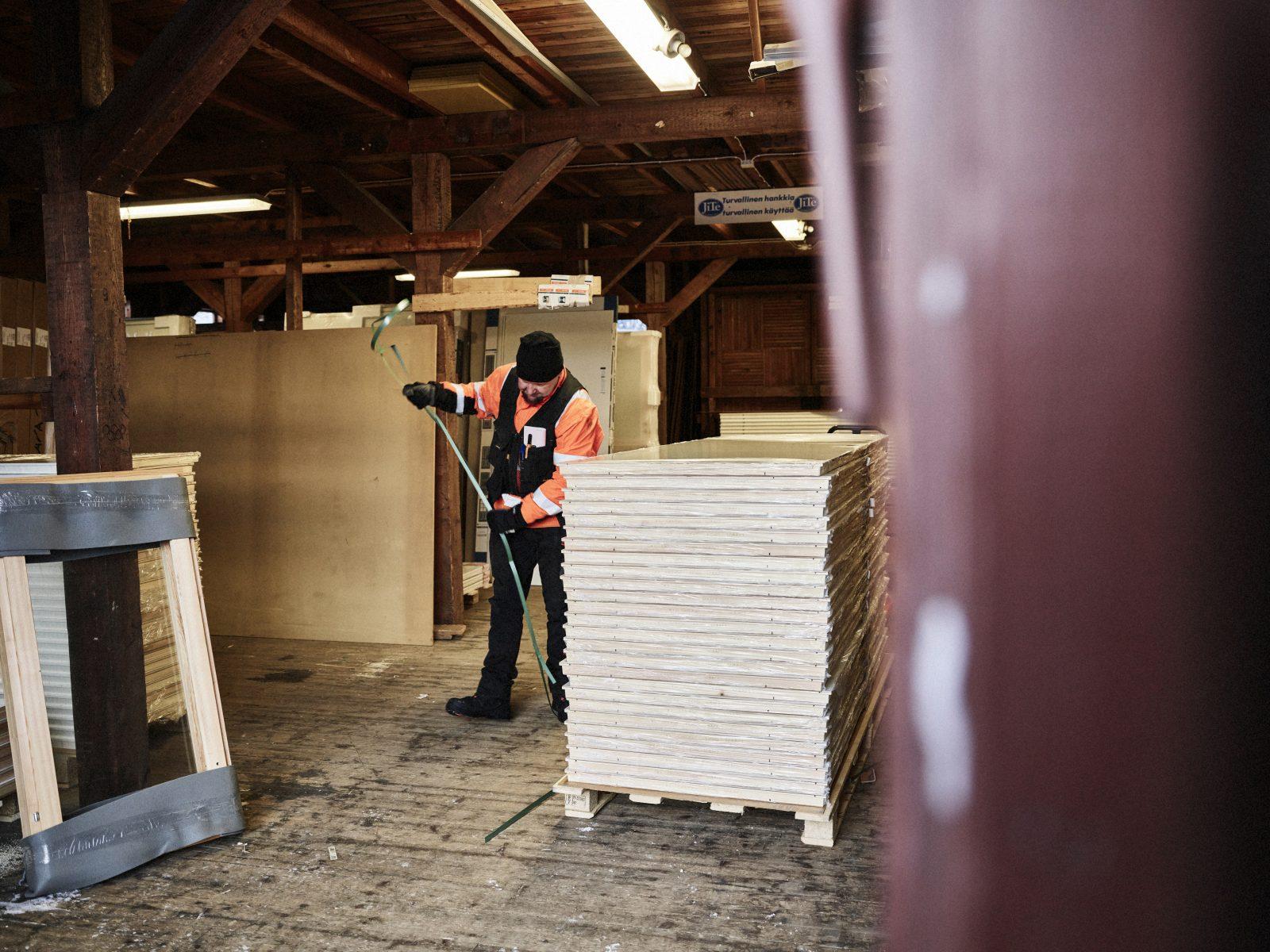 Varastötyöntekijä pakkaamassa väliovilavaa.